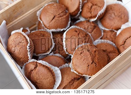 Chocolate muffins closeup in wooden tray. Plenty of chocolate cocoa muffins fresh baked for sale at country fair. Sweet food, snacks, desserts background. Bakery products
