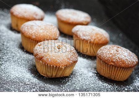 muffins in powdered sugar on a dark table