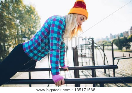 Young beautiful woman preparing to do push ups on parallel bars at calisthenics park, looking off the camera
