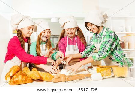 Four kids, young bakers in cook's uniform, kneading dough with flour and eggs in the kitchen
