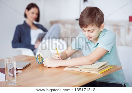 Very efficient homework session. Boy writing in notebook, sitting at desk with her mother in background, using digital tablet