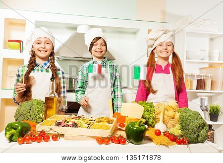 Three young cooks, girls and boy in aprons and cook's hats preparing traditional Italian meal, holding small flags of Italy