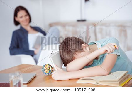 Too many study sessions. Young boy feeling asleep after hard studying with her mother in background, using digital tablet