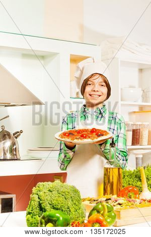 Young cook, boy in white apron and hat, holding plate with tasty pizza in the kitchen