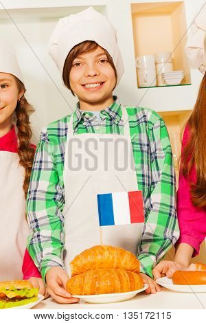 Young baker, smiling boy in apron and cook hat with plate of fresh tasty French croissants