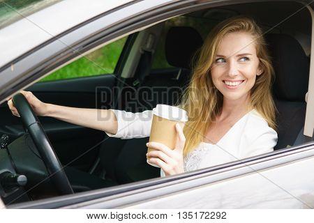 Smiling young bautiful woman sitting in car