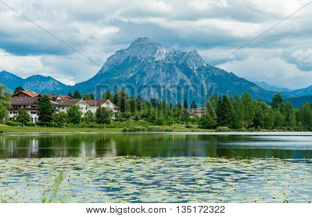 Lake in the German Alps with a chain of mountain peaks on the horizon. Reflection of the sky in water