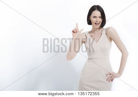Pointing at your copyspace. Waist up of beautiful woman in cream dress showing copy space, isolated on white background
