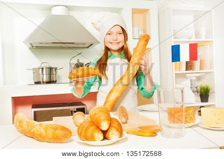 Smiling girl in cook's uniform with traditional French baguettes and croissants at the kitchen
