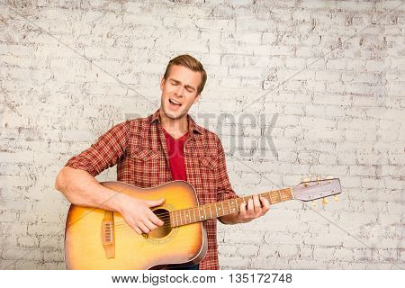 Handsome Young Man In Red Shirt  Playing On The Guitar
