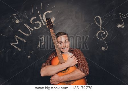 Happy Young Smiling Musician Huging His Guitar
