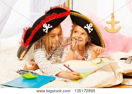 Two smiling girls in pirate's tricorns, drawing the treasure map with the colored pencils