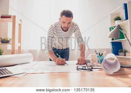 Concentrated Young Engineer Working On Plane Of New House