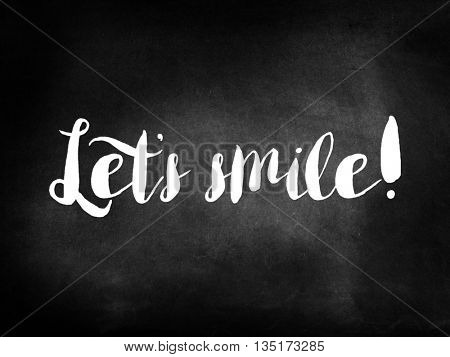 Let's smile written on a chalkboard