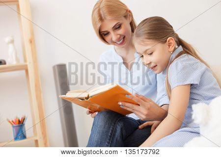 Story time. Cropped shot of young mother reading to her daughter at home