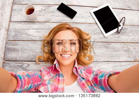 Cheerful Blonde With Beaming Smile Lying On Floor And Making Selfie