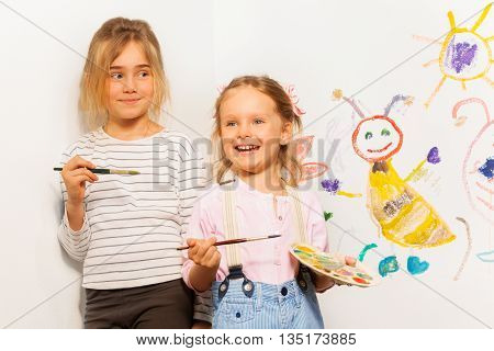 Two smiling painters, girls with pallet and brushes drawing funny picture on the wall