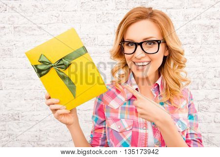 Cheerful Happy Woman In Glasses Pointing Yellow Box