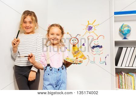 Two happy girls, young painters with brushes and pallet, drawing funny picture at the wall