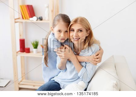 Be good girl for me. Cute little girl smiling while hugging her mother tightly, sitting on sofa