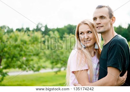 Young couple standing in park and hugging