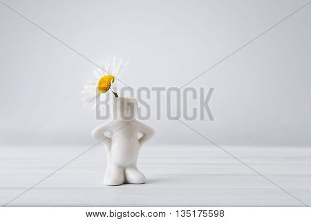 Beautiful daisy in small white ceramic vase in form of man on white table at neutral background. Small man with flower head. Flower with copy space. Funny vase.