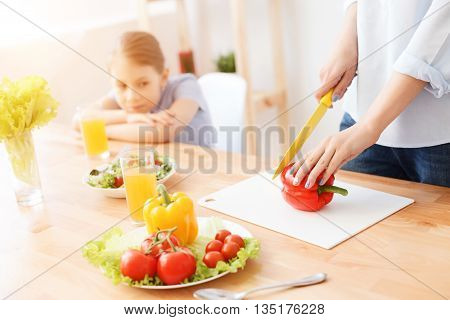 Delicious salad in the making. Close up of little girl watching her mother choping vegetables in kitchen