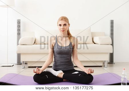 Find your happy place. Attractive young woman meditating in yoga pose, sitting on the floor at home