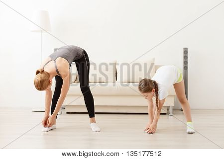I can touch my toes. Young mother and daughter doing doing fitness exercises at home