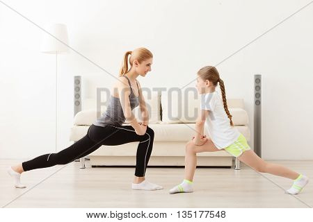 Fitness for the mind and body. Mother and daughter doing yoga exercise and stretching
