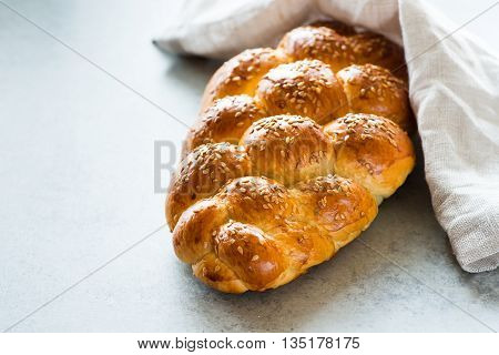 Homemade challah bread with sesame seeds over grey background selective focus
