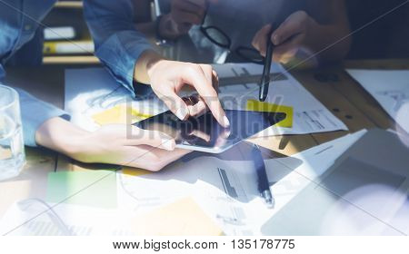 Woman Touching Display Modern Tablet Hand.Reflections Screen.Project Producers Researching Process.Young Business Team Working New Startup Studio.Analyze market stock.Blurred, film effect.Horizontal