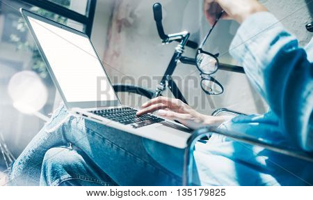Work process modern design Studio Loft.Creative copywriter working coworker office freelance business startup.Using Laptop knees, holding glasses hand.Horizontal mockup.Flares effect.Blurred background