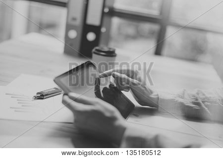 Internet surfing Process in Modern Office. Young Account Manager Working at Wood Table with New Business Project.Touching Screen Digital Tablet. Horizontal.Film effect. Blurred background. Black White