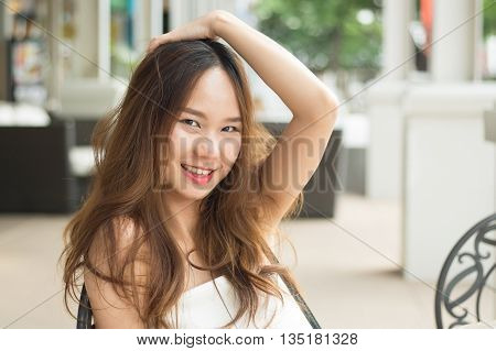 Asian beautiful girl raise hand higher and put hand over head and smile