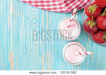Strawberry milkshake in the glass jar with drinking straw on blue wooden table. Top view