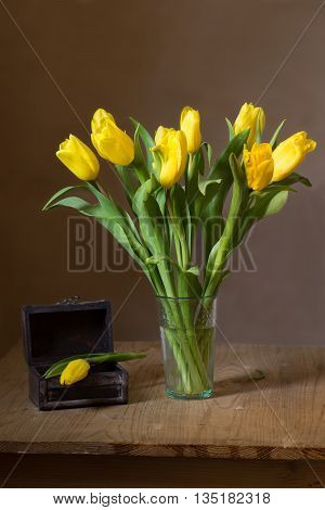 Still life with a bunch of yellow tulips and trinket box on wooden table