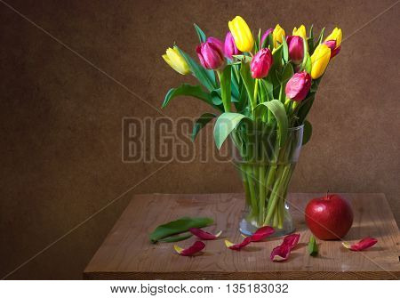 Still life with red and yellow tulips and red apple on wooden table