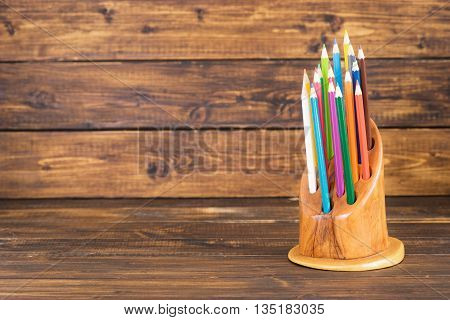 Colored pencils in a wooden stand for school and kindergarten on a dark wood background