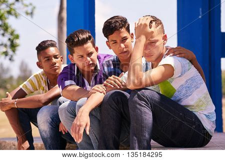 Youth culture young people group of male friends multi-ethnic teens outdoor teenagers together in park. Boys comforting sad friend kids helping depressed boy. Adolescence bond relationship