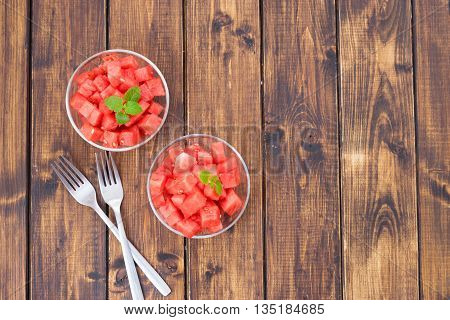 Watermelon cut in small peaces or cubes in two glass dishes on wooden background- Top view.