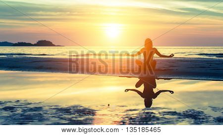 Young healthy woman silhouette practicing yoga on the beach at sunset.