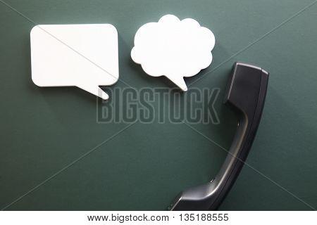 handset with speech bubble on the blackboard