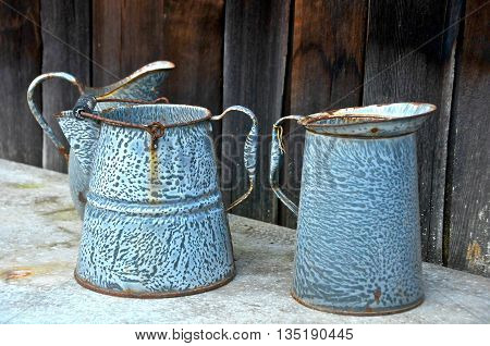 Rusted old coffee pot and pitcher on a shelf against a wooden wall.