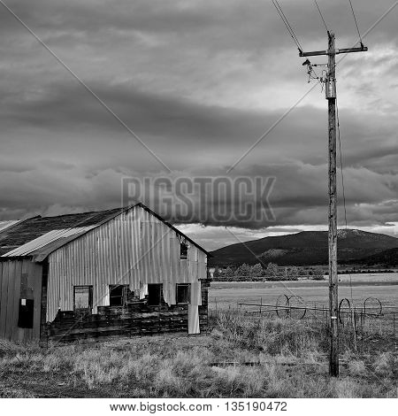An old worn down building in the country stands by a no longer needed electrical pole while a storm blows through.