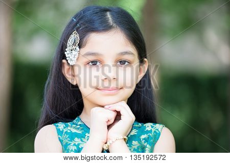 Closeup portrait young girl resting placing face on hands isolated outside outdoors background