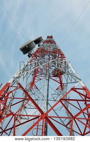Satellite dish telecoms on telecommunications tower on blue clear sky