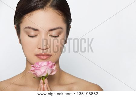 Studio shot of a beautiful young Asian Japanese woman holding smelling a pink rose between her clasped hands with eyes closed in meditative contemplation