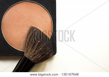 Correcting powder brusher and brush on white background with copy space. Makeup product to even out skin tone and complexion. Professional cosmetics.