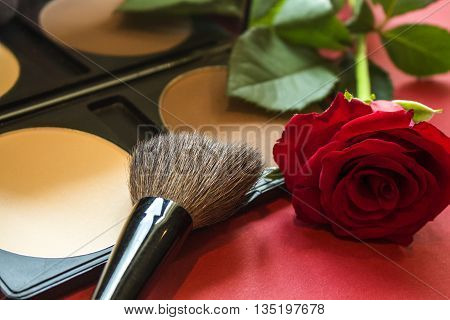 Close-up correcting powder brush and rose on red textured surface. Makeup product to even out skin tone and complexion. Professional cosmetics. Rose reflecting in the mirror. Close-up image artistic retouching.